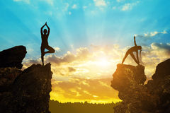 Silhouette of a girls doing yoga on a rock Royalty Free Stock Photos