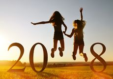 Girls jumping up at the celebration of New Year 2018. Silhouette of girls jumping up in the sunset at the celebration of New Year 2018 Stock Photos