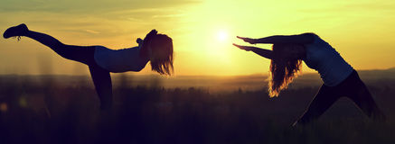 Silhouette girls stretching on a meadow Royalty Free Stock Images
