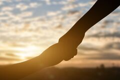 Silhouette of giving a help hand, hope and support each other over sunset