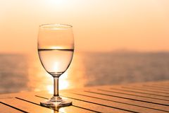 Silhouette glass of wine on a wooden table with seascape and sk. Yline in the evening with sunset tone style stock photo