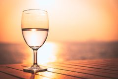 Silhouette glass of wine on a wooden table with seascape and sk. Yline in the evening with sunset tone style royalty free stock photography