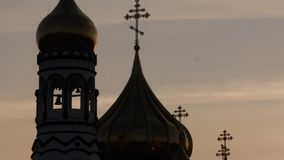 Silhouette of golden church dome on sunrise sky, Christian cross on top of church tower. 4K. Silhouette of golden church dome on sunrise sky, Christian cross on stock footage
