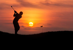 Silhouette golfer hitting golf ball in sunset. Silhouette golfer hitting golf ball toward the hole at sunset Royalty Free Stock Image