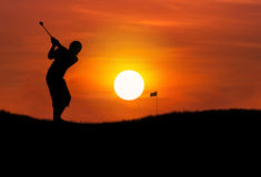 Silhouette golfer hitting golf ball at sunset. Silhouette golfer hitting golf ball toward the hole at sunset Royalty Free Stock Image