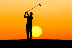 Silhouette golfer hitting golf. On sunrise Royalty Free Stock Photos