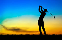 Silhouette golfer playing golf at beautiful sunset Royalty Free Stock Photos