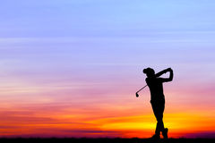 Silhouette golfer playing golf at beautiful sunset Royalty Free Stock Image