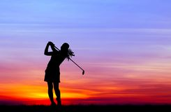 Silhouette golfer playing golf at beautiful sunset
