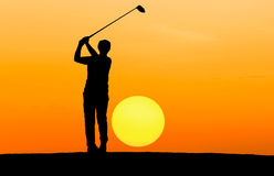 Silhouette golfer playing golf. On sunrise Stock Photo