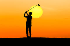Silhouette golfer playing golf. On sunset Stock Image