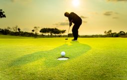 Silhouette golfer showing happiness when win in game , white golf ball on green grass with blur background.