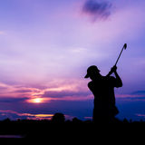 Silhouette golfer at sunset Stock Image