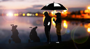 Silhouette of golfers hit sweeping and keep golf course in the summer for relax time.  Royalty Free Stock Images
