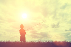 Silhouette grass and little boy fishing with sky and clouds during sunset Royalty Free Stock Photo
