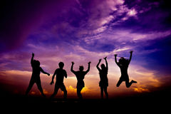 Silhouette group of friends having fun jumps Stock Image