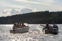 Silhouette of people racing with powerboats. Silhouette of group of friends racing with powerboats on lake Stock Photo