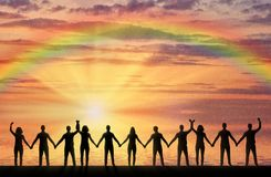 Silhouette of a group of happy people holding hands by the sea at sunset with a rainbow
