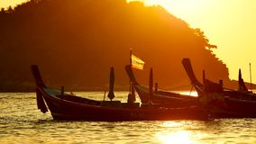 Silhouette group of long tail boat convertedfloating in the andaman sea with golden light. Silhouette group of long tail boat converted to boat excursions and stock video footage