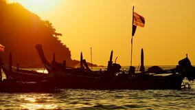 Silhouette group of long tail boat convertedfloating in the andaman sea with golden light. Silhouette group of long tail boat converted to boat excursions and stock video