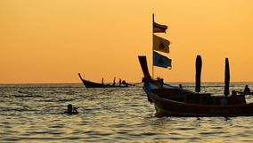 Silhouette group of long tail boat convertedfloating in the andaman sea with golden light. Travel video Silhouette group of long tail boat converted to boat stock footage