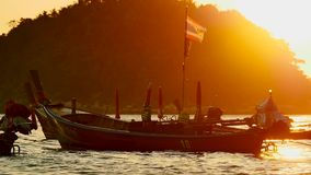 Silhouette group of long tail boat convertedfloating in the andaman sea with golden light. Travel video Silhouette group of long tail boat converted to boat stock video footage