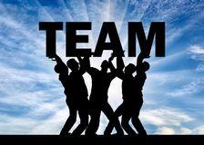 Silhouette of a group of men who hold the word team above themselves. The concept teamwork royalty free stock photography
