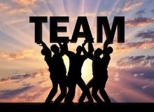 Silhouette of a group of men who hold the word team above themselves. The concept of a business team and teamwork royalty free stock photography