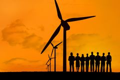 silhouette of group of people with windmills on orange sky background Royalty Free Stock Image