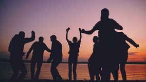 Silhouette of Group young dancing people have a party at beach on sunset stock photography