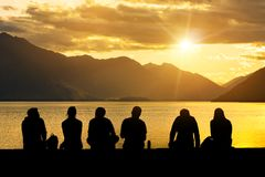 Silhouette Group of Young People Sitting on Beach. Silhouette group of young people sitting on lake beach against mountain landscape at sunset showing concept of Royalty Free Stock Image