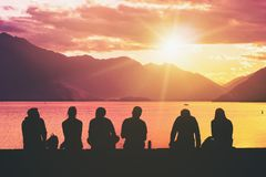 Silhouette Group of Young People Sitting on Beach. Silhouette group of young people sitting on lake beach against mountain landscape at sunset showing concept of Royalty Free Stock Images