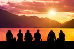 Silhouette Group of Young People Sitting on Beach. Silhouette group of young people sitting on lake beach against mountain landscape at sunset showing concept of Stock Image
