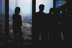 Silhouette of a group young purposeful financiers lead a conversation while standing in modern office interior stock photos