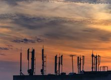 Silhouette of GSM antennas with dusk sky Royalty Free Stock Photos