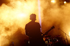 Silhouette of guitar player in action on stage. Silhouette of guitar player in action on concert stage royalty free stock images