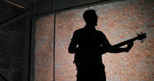A silhouette of a guitar player, brick wall background. A silhouette of a guitar player. Man lead guitarist playing electrical guitar stock video footage