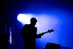 Silhouette of a guitar player on the stage. Smoke and stage lights Stock Photos