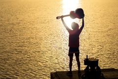Silhouette of guitarist playing a guitar on the river under the Royalty Free Stock Photos