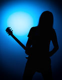 Silhouette guitarists of a rock band with guitar on blue background Royalty Free Stock Image