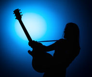 Silhouette guitarists of a rock band with guitar on blue background Stock Image