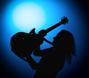Silhouette guitarists of a rock band with guitar on blue background Royalty Free Stock Photos