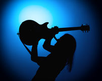 Silhouette guitarists of a rock band with guitar on blue background Stock Photo