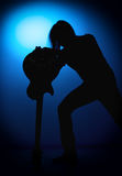 Silhouette guitarists of a rock band with guitar on blue background Royalty Free Stock Photography