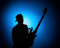 Silhouette guitarists of a rock band with guitar on blue background Stock Photography