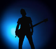 Silhouette guitarists of a rock band with guitar on blue background. Silhouette guitarists of a rock band with a guitar on a blue background Royalty Free Stock Image