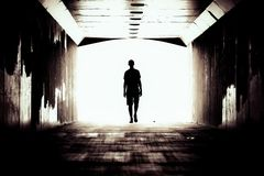 Silhouette of a guy in a dark tunnel royalty free stock photography