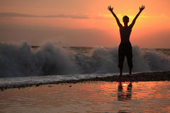 Silhouette guy lifted hands upwards on sunset Stock Image