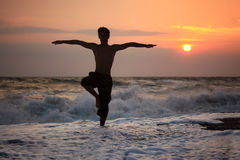 Silhouette guy yoga on sunset wavy beach Stock Photos