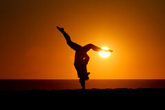 Silhouette of gymnast on beach at sunset Stock Image
